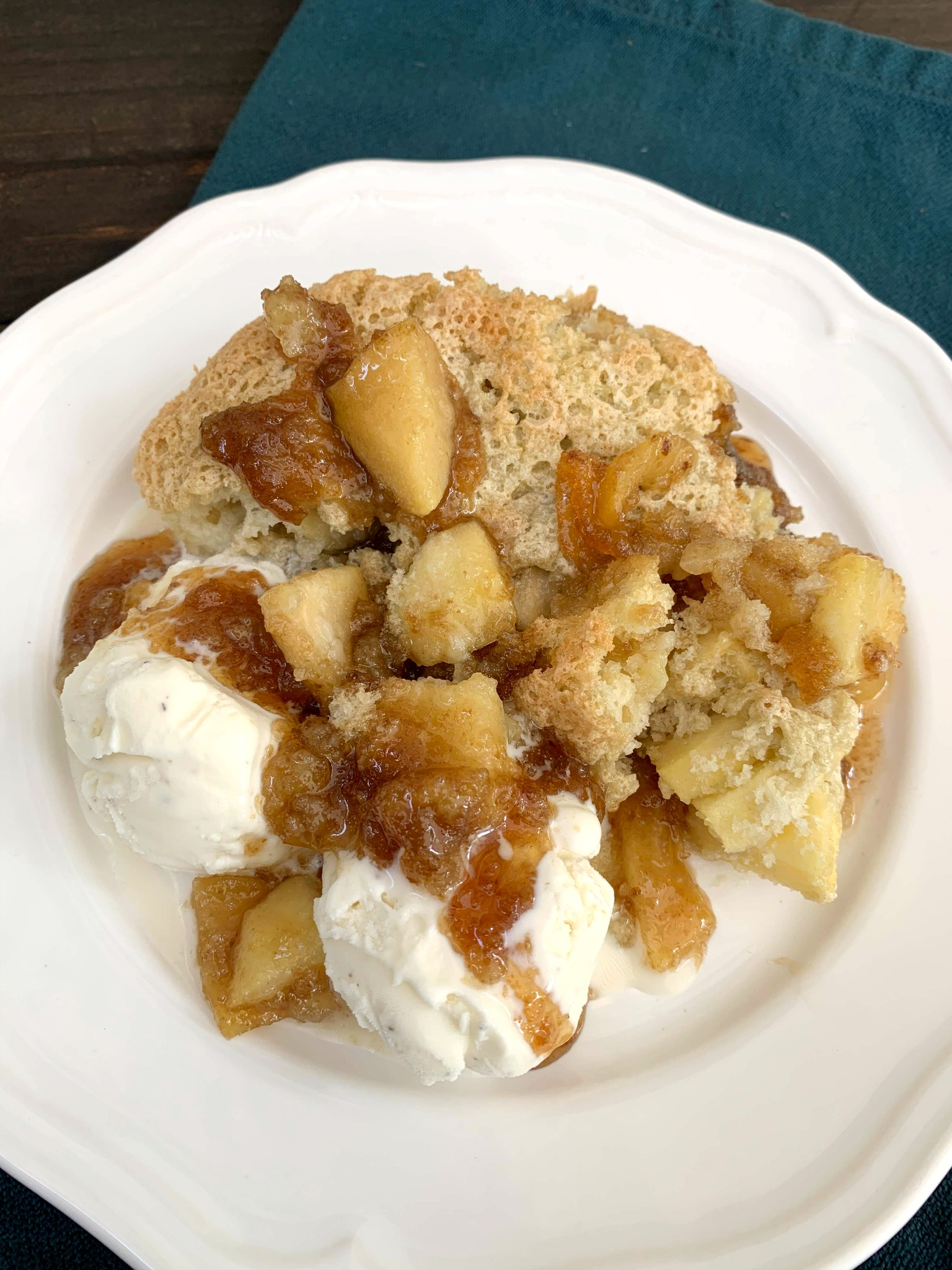 a serving of apple pudding cake on a white plate with two scoops of vanilla ice cream