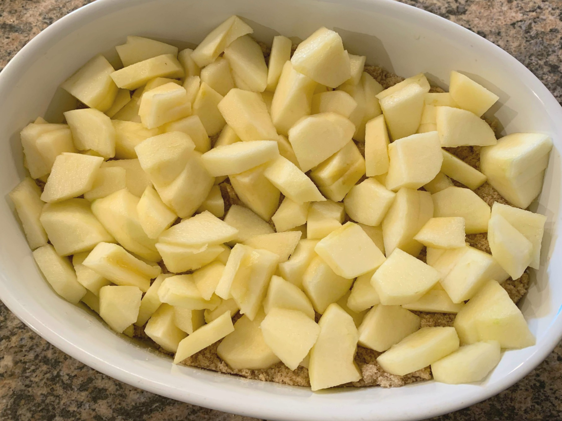 a white oval dish with chopped apples