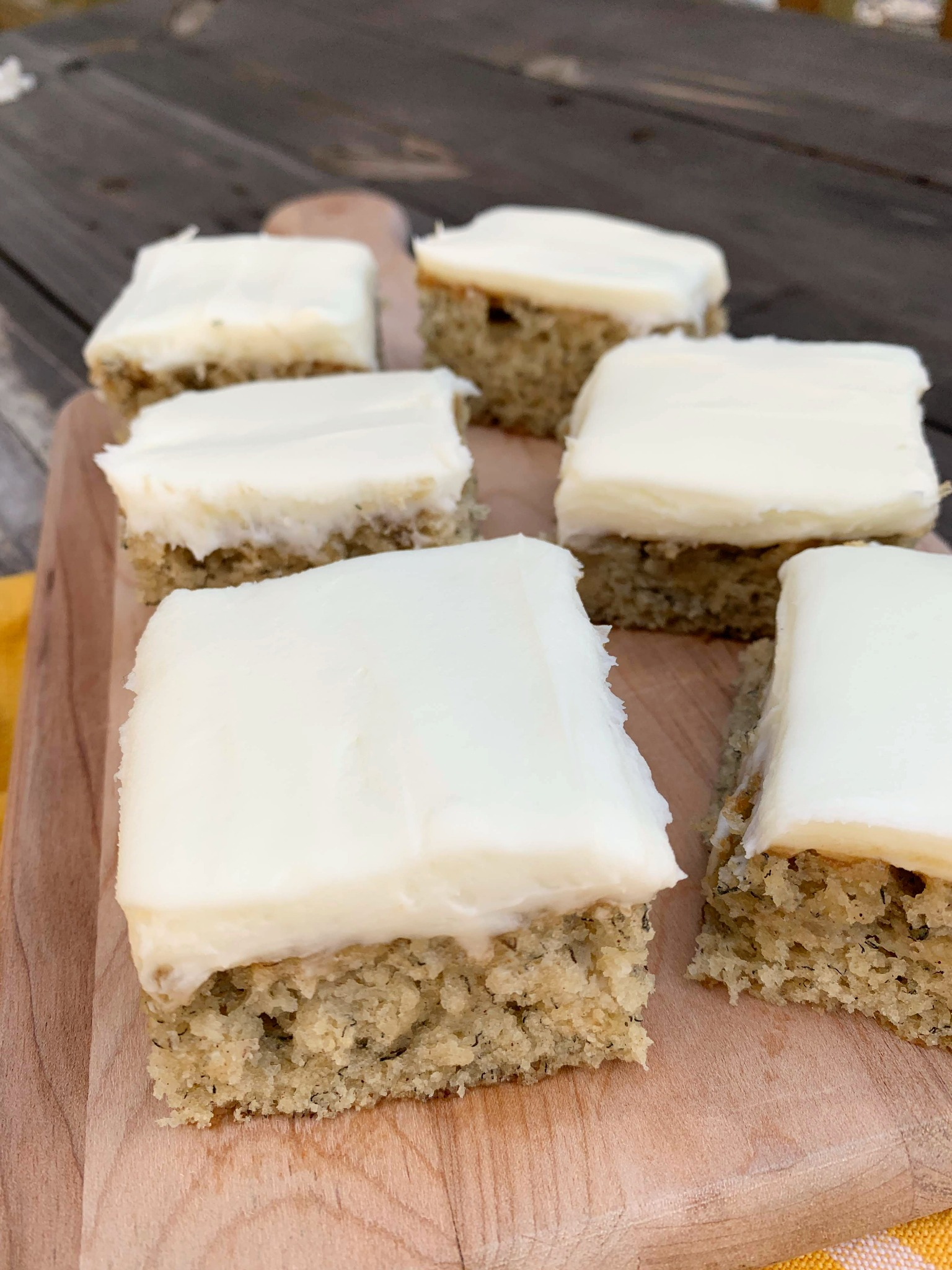 a wooden cutting board with slices of banana sheet cake with cream cheese frosting