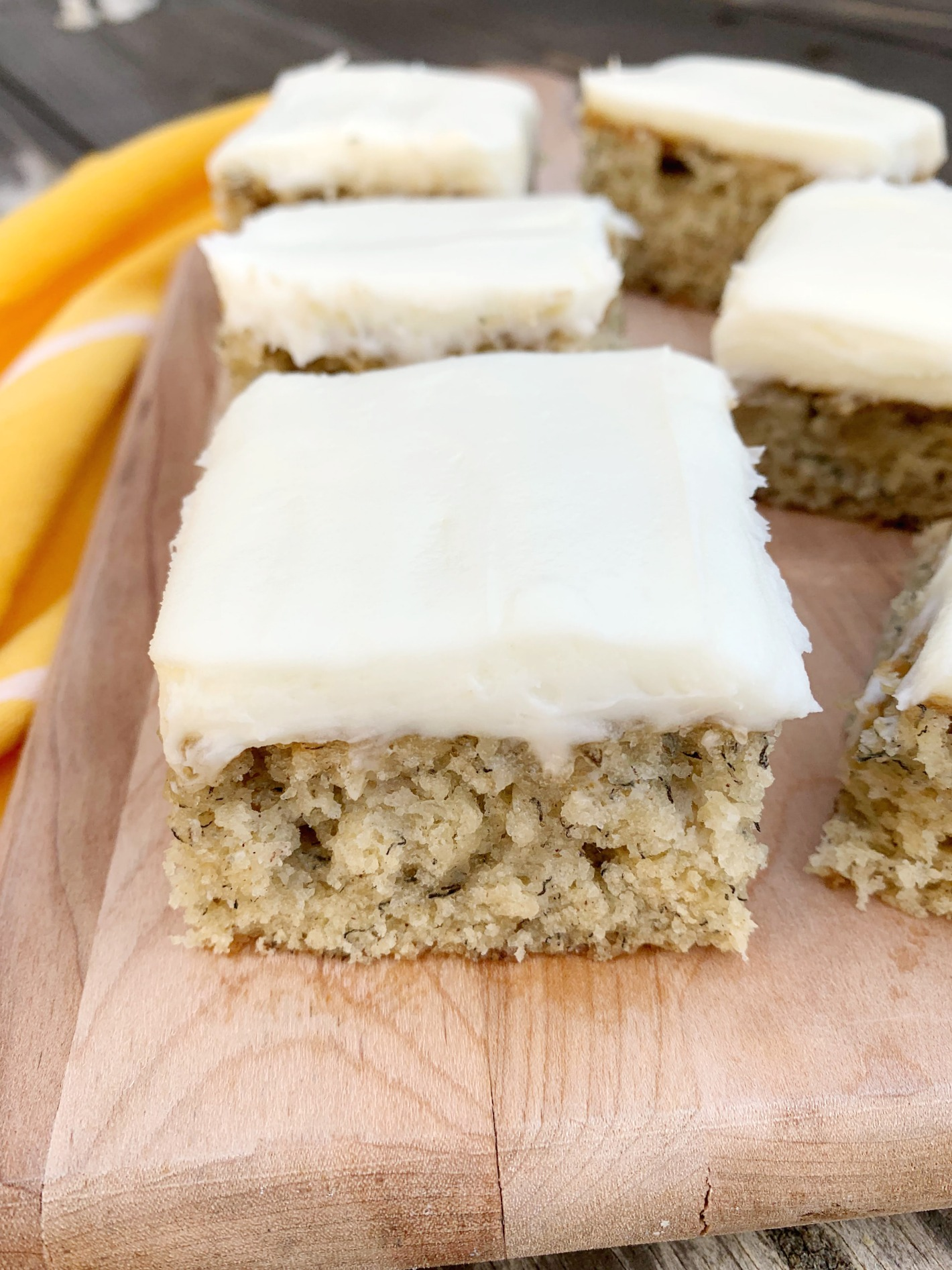 wooden cutting board with an upclose shot of a banana cake slice with cream cheese frosting