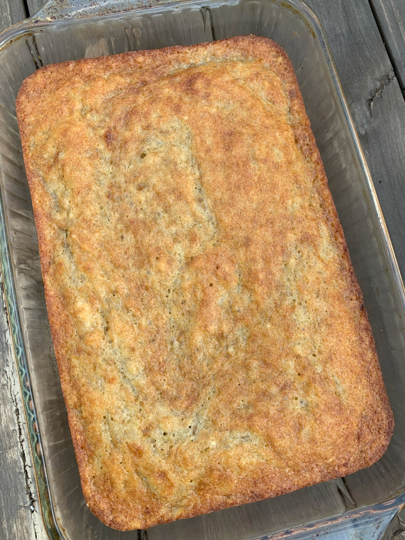 a glass 13x9 pan with a baked banana cake in it
