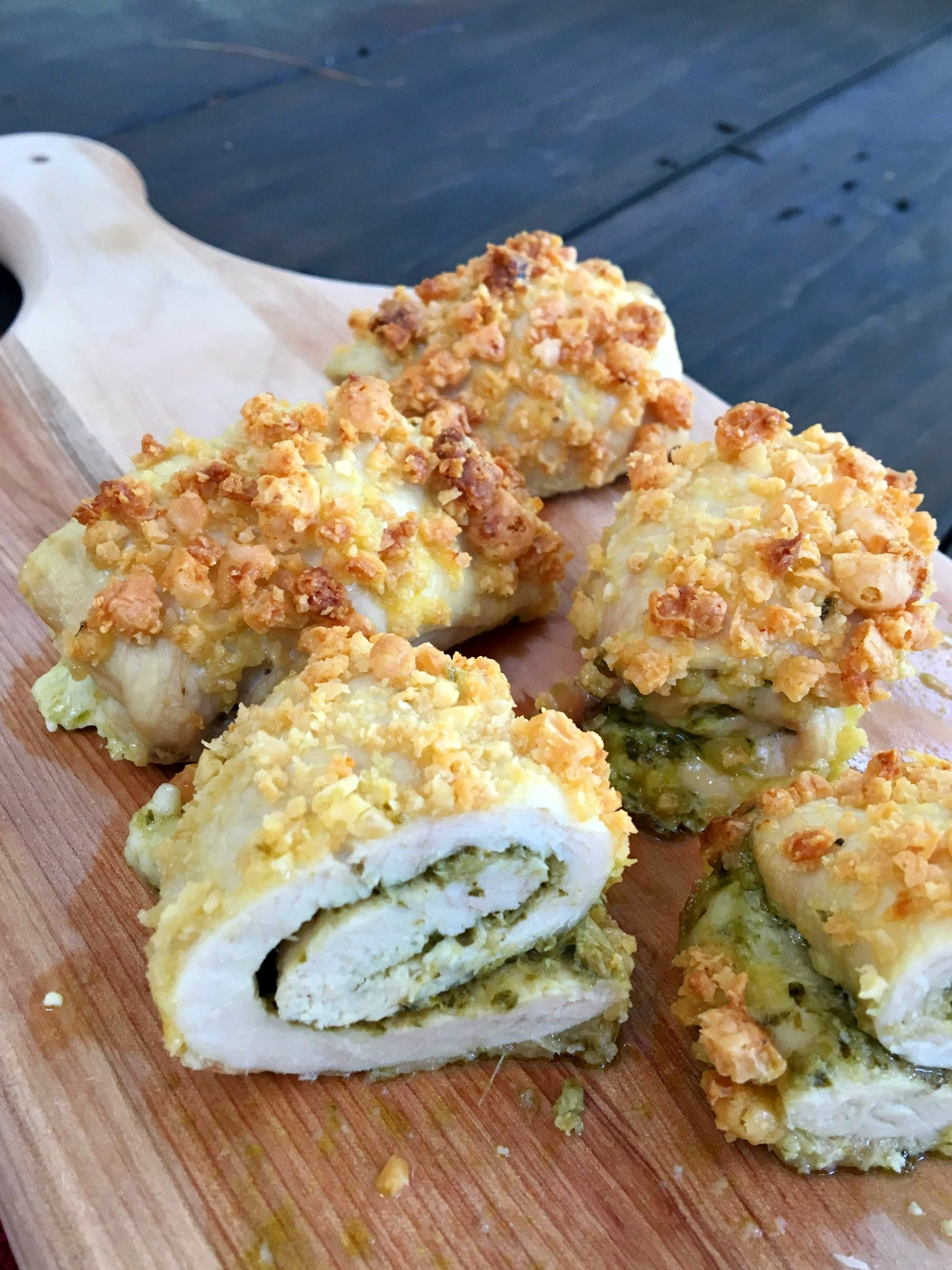 Chicken roll-ups cut in half on a wooden cutting board
