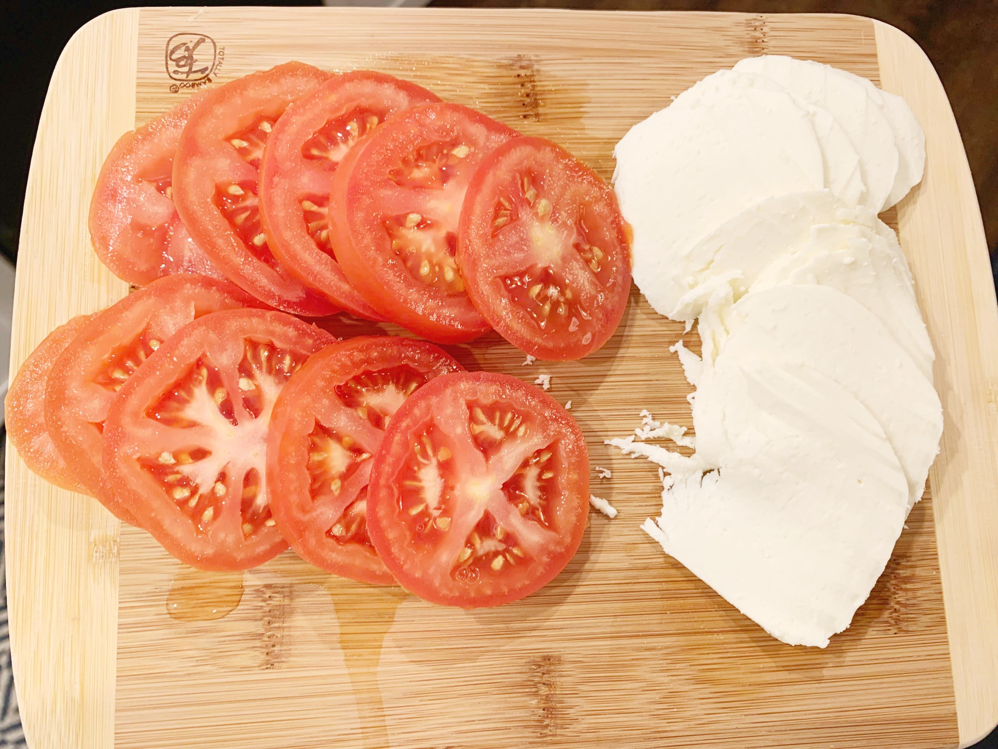 wood cutting board with sliced tomatoes and sliced mozzarella
