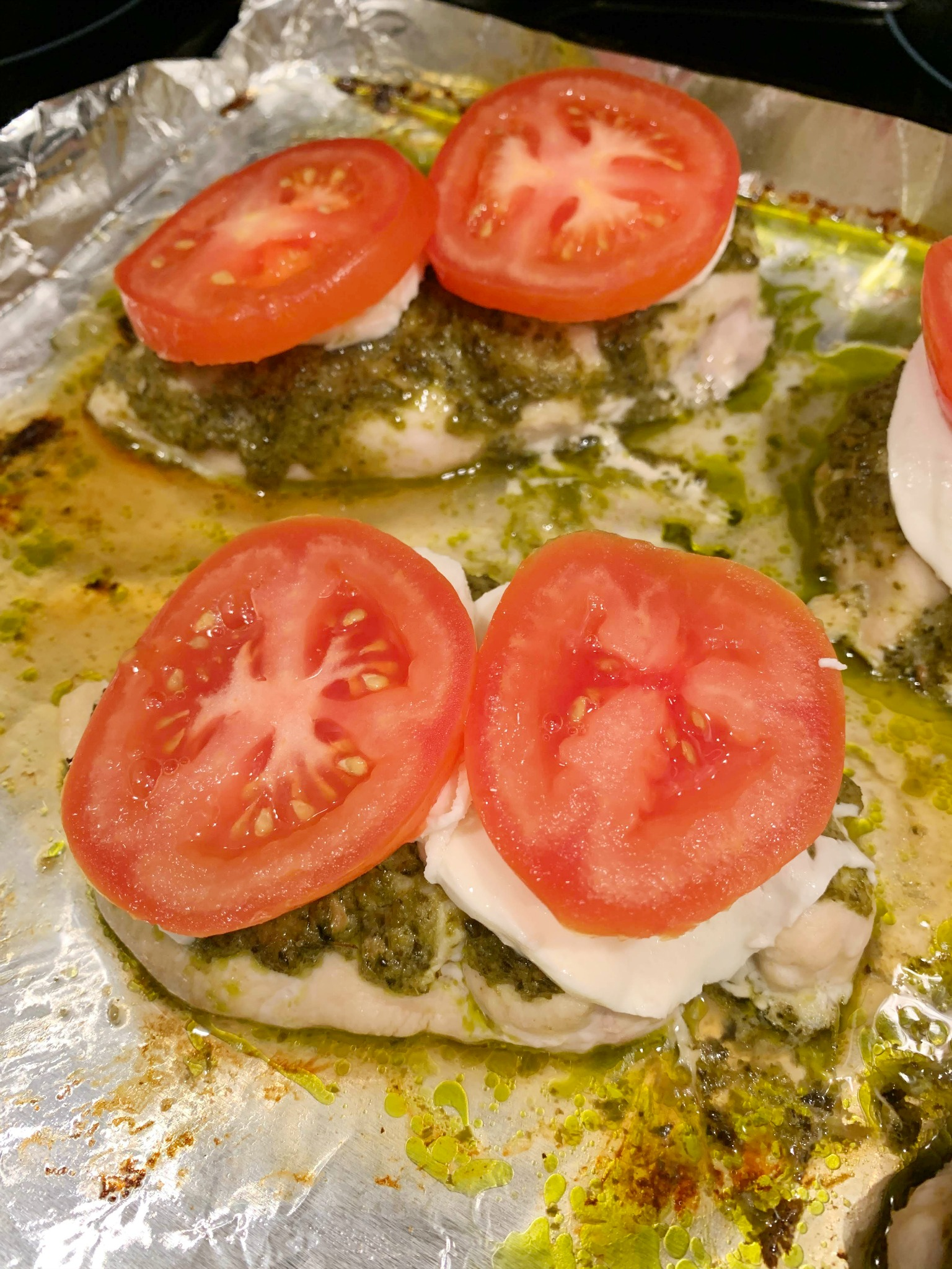 up close chicken breasts topped with pesto, mozzarella and tomato slices on a foil lined baking sheet