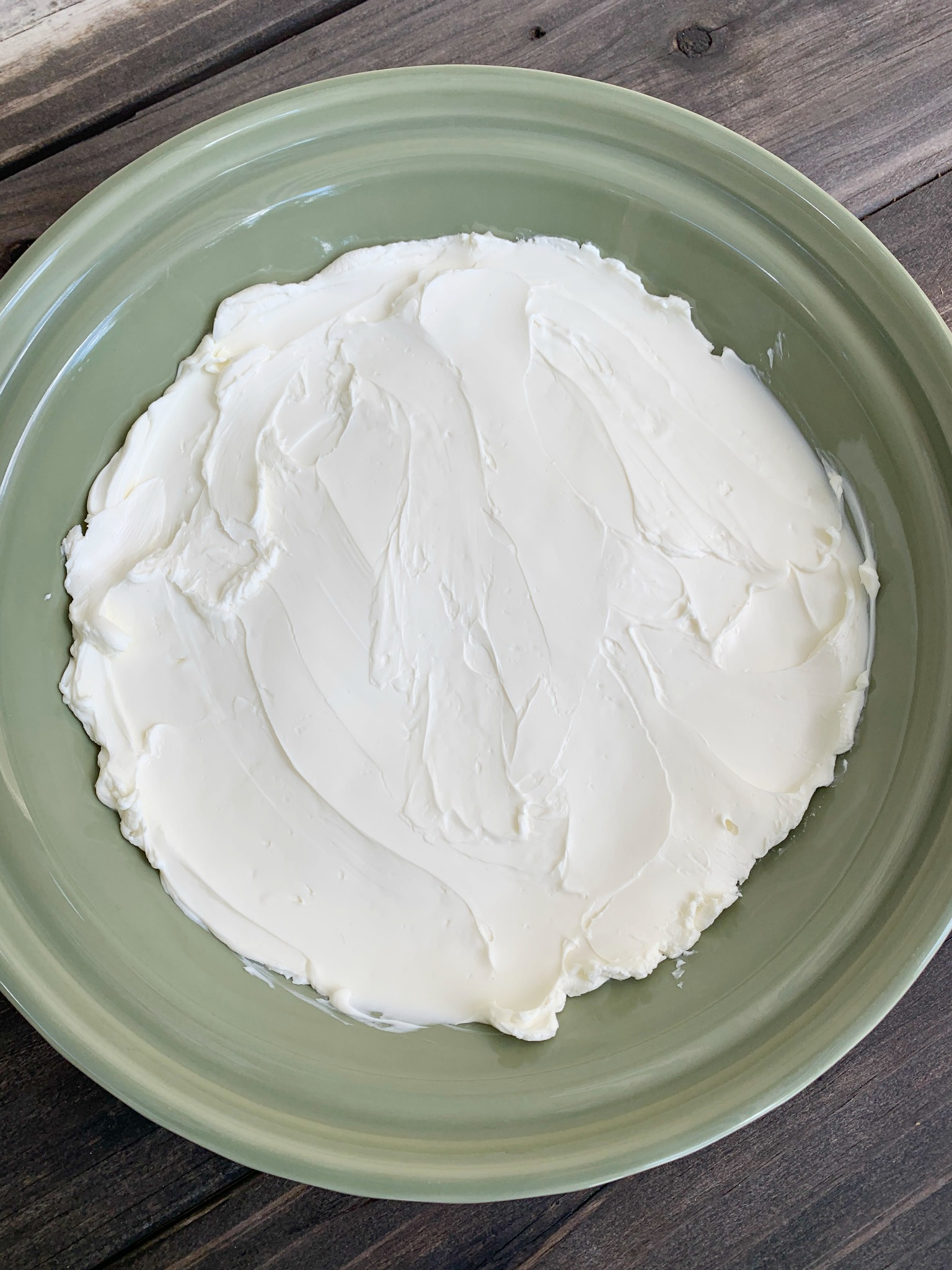 a green pie dish with a layer of cream cheese