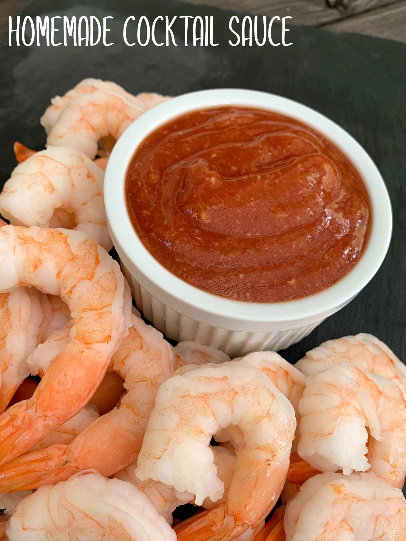 white bowl of cocktail sauce with shrimp around it