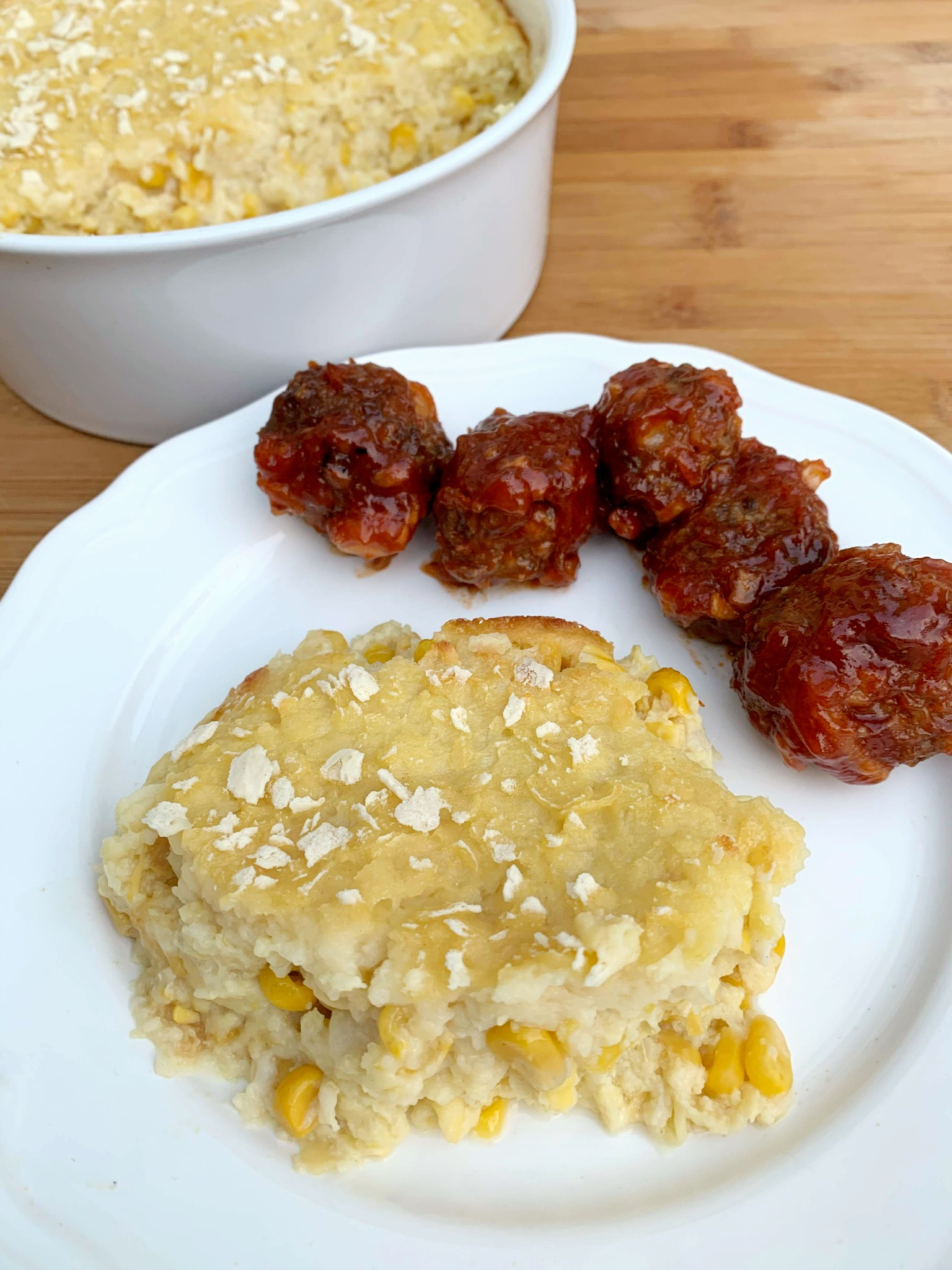 a serving of scalloped corn on a plate with meatballs in the background