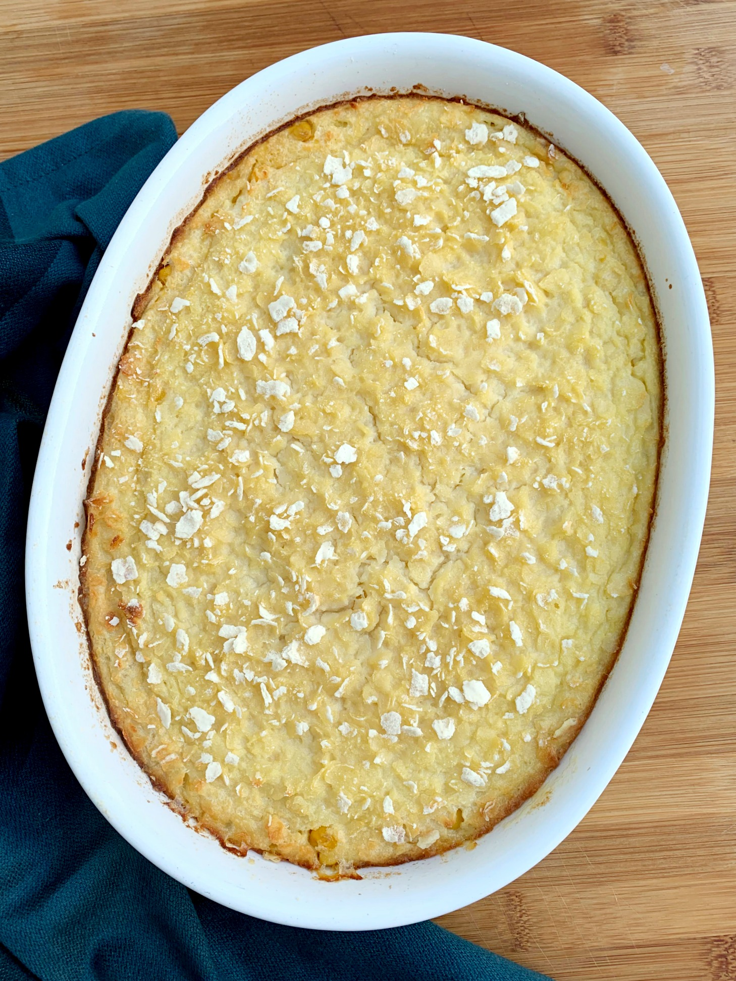 a white oval dish with baked scalloped corn