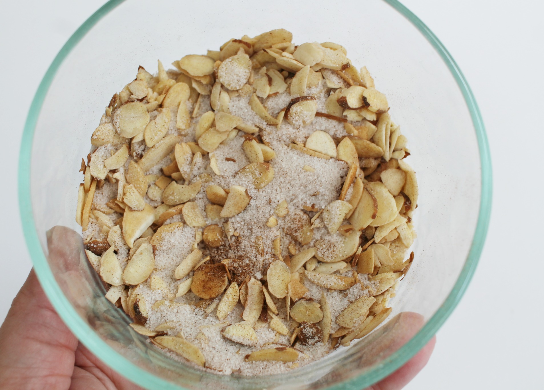 a glass bowl of sliced almonds mixed with cinnamon and sugar
