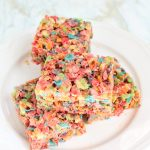 round white plate with 4 squares of Fruity Pebbles Rice Krispies stacked on top of each other