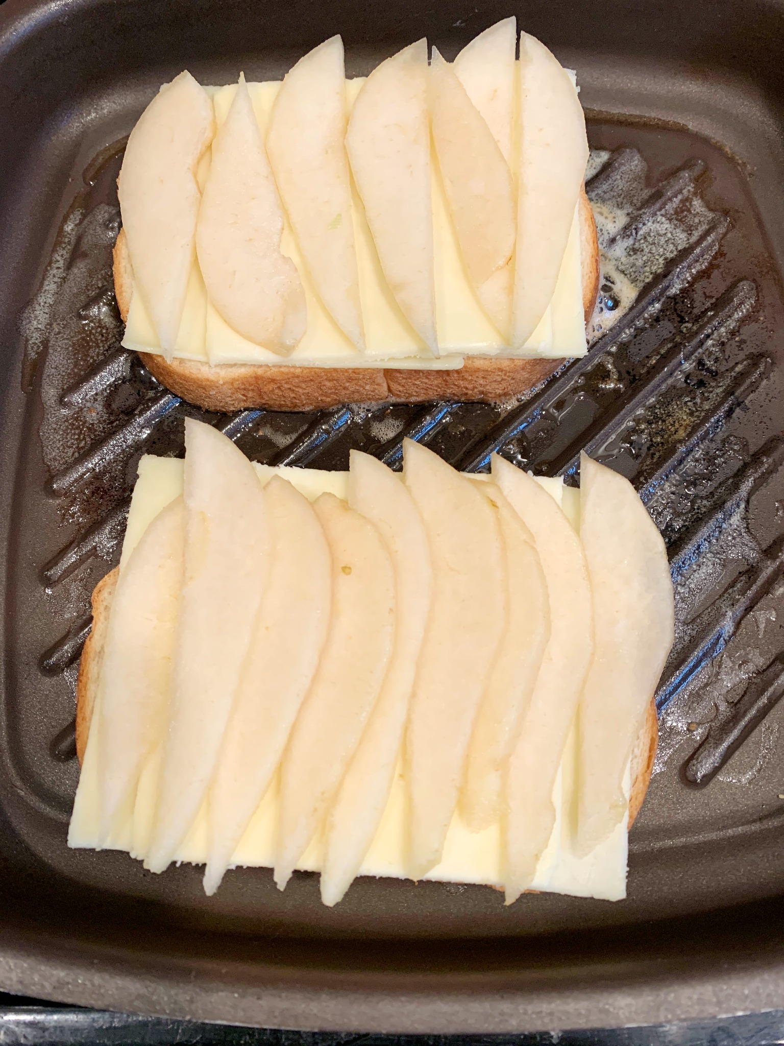 a cast iron grill pan with 2 slices of bread topped with cheese and sliced pears
