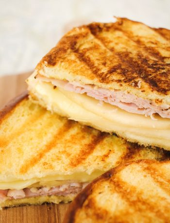 upclose shot of half of a grilled ham, pear and cheese sandwich