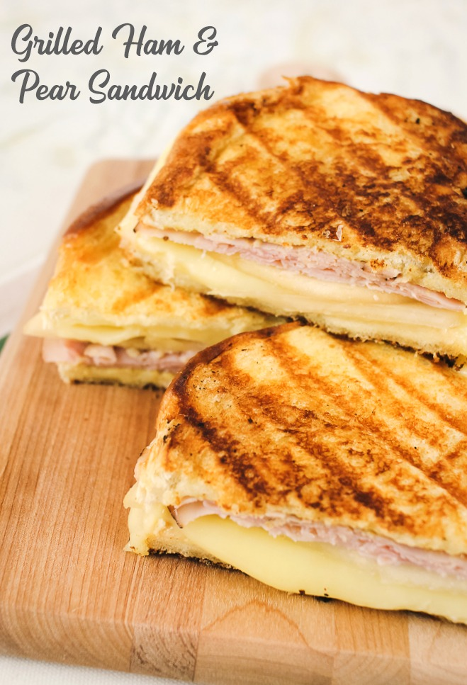 a ham, pear and grilled cheese sandwich with halves piled on top of a wooden cutting board