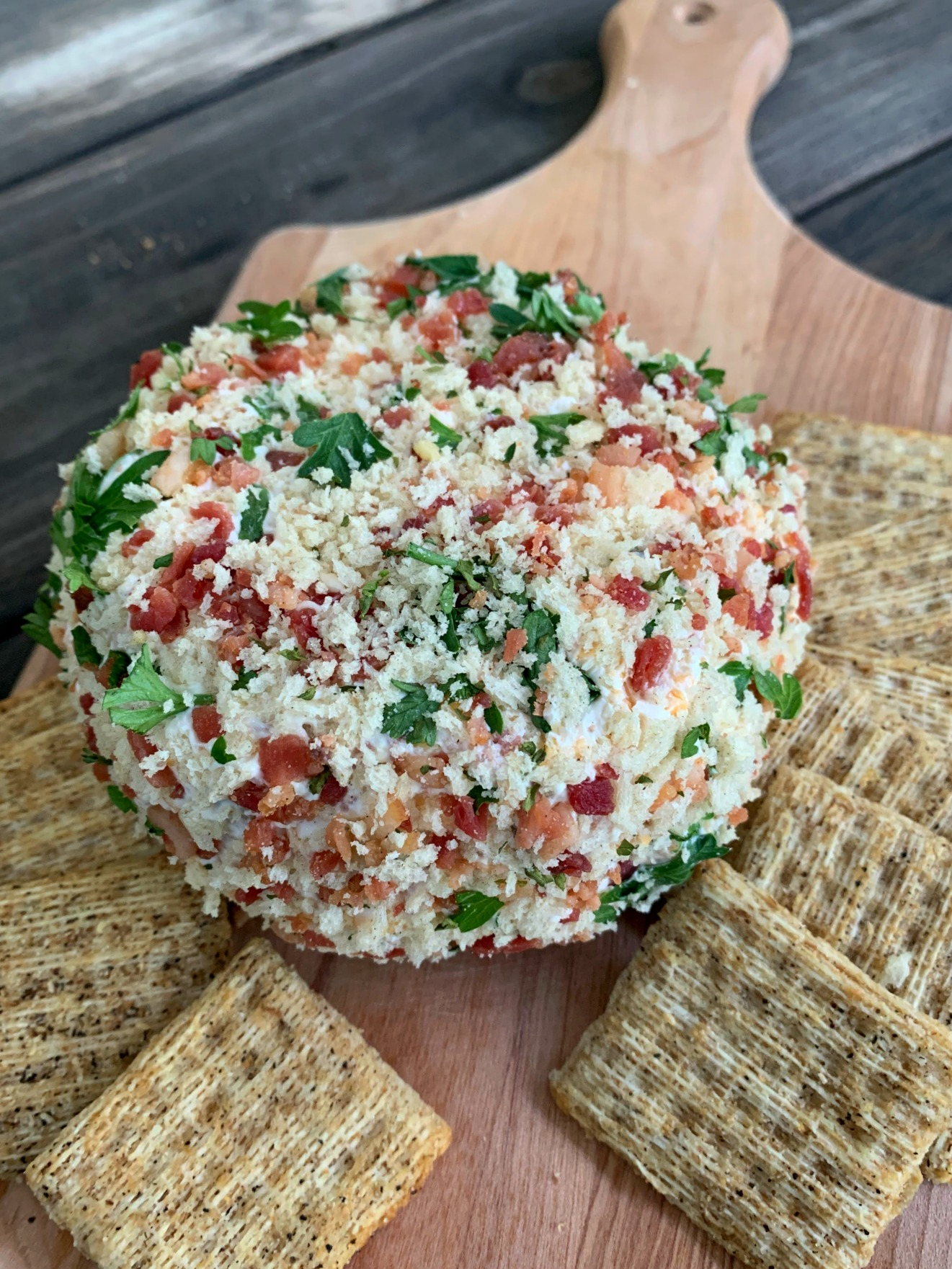 jalapeno cheese ball on a wooden cutting board with crackers around it