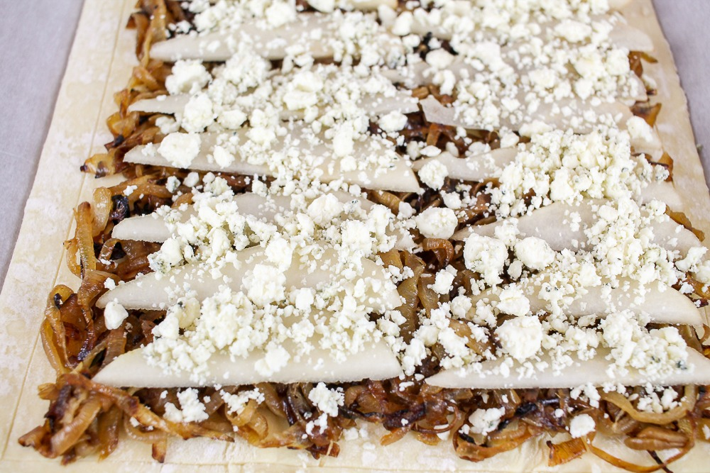uncooked sheet of puff pastry topped with caramelized onions, thinly sliced pears and gorgonzola cheese
