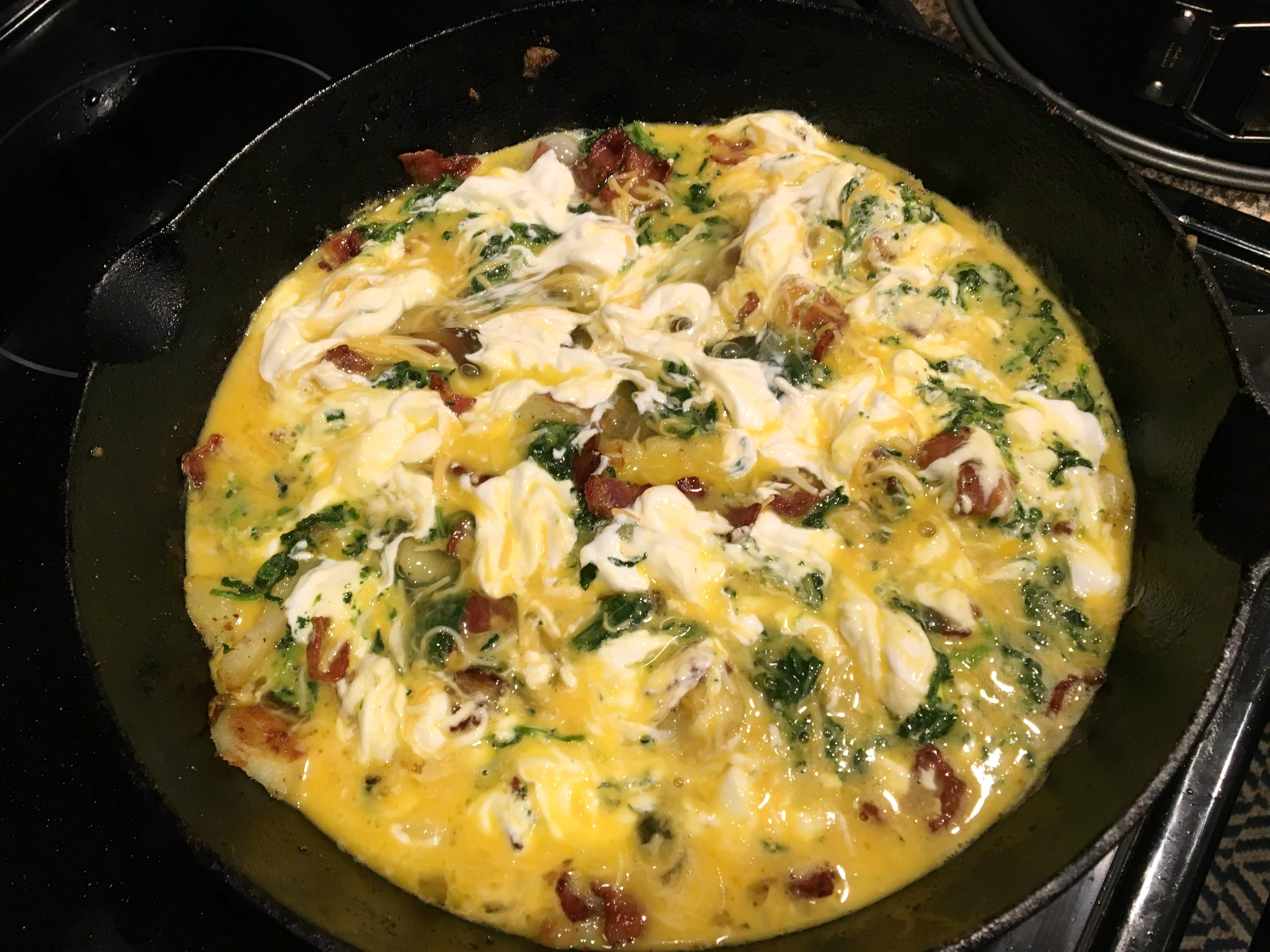 a cast iron pan with uncooked frittata
