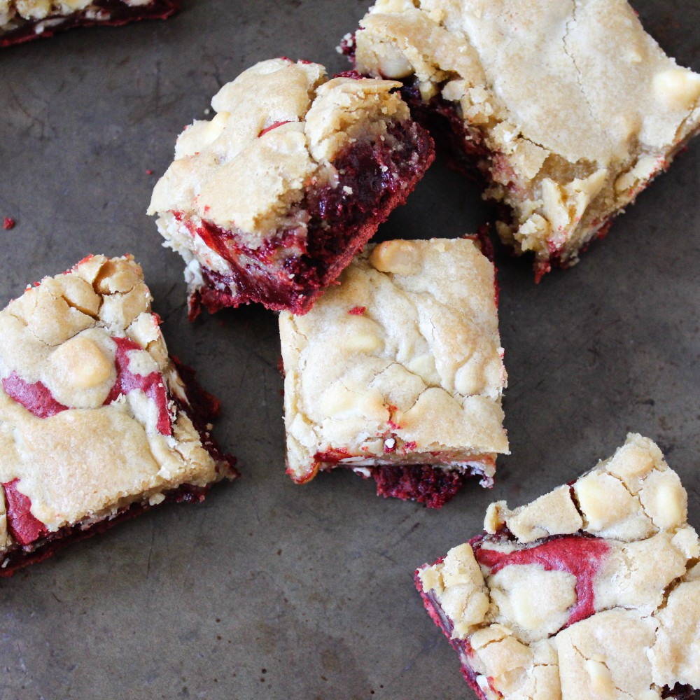 red velvet macadamia nut brownies cut into squares and piled on a piece of slate