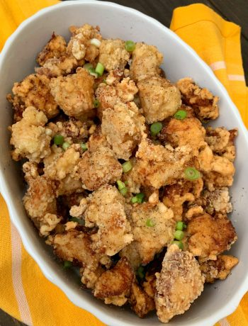 oval text with salt and pepper chicken sprinkled with sliced green onions with a yellow towel in the background