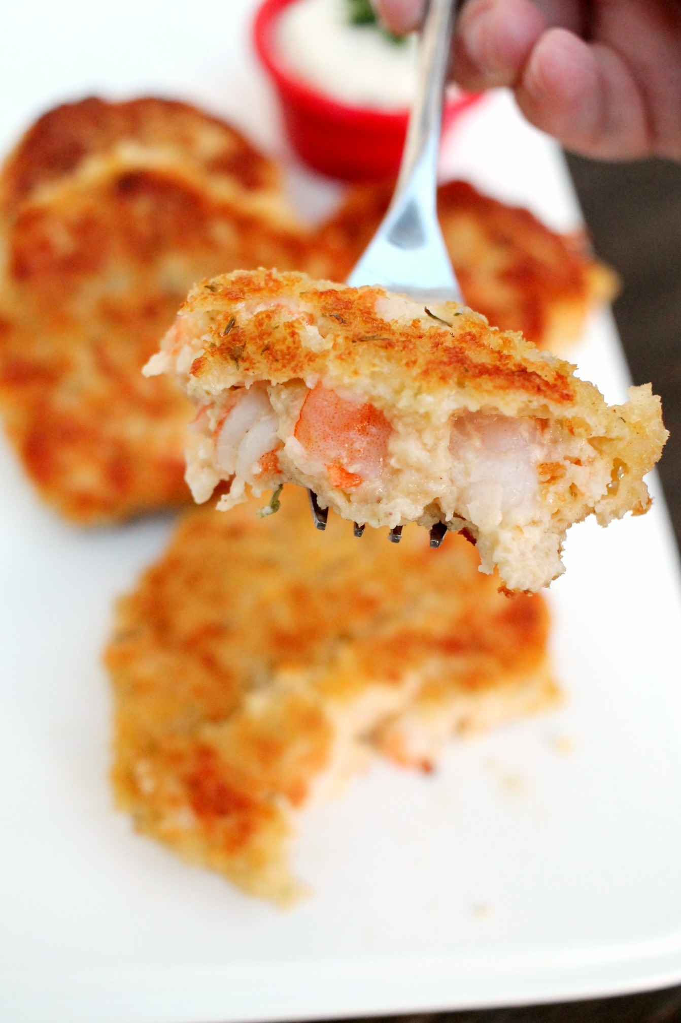 a fork holding a bite of a shrimp cake with whole shrimp cakes in the background