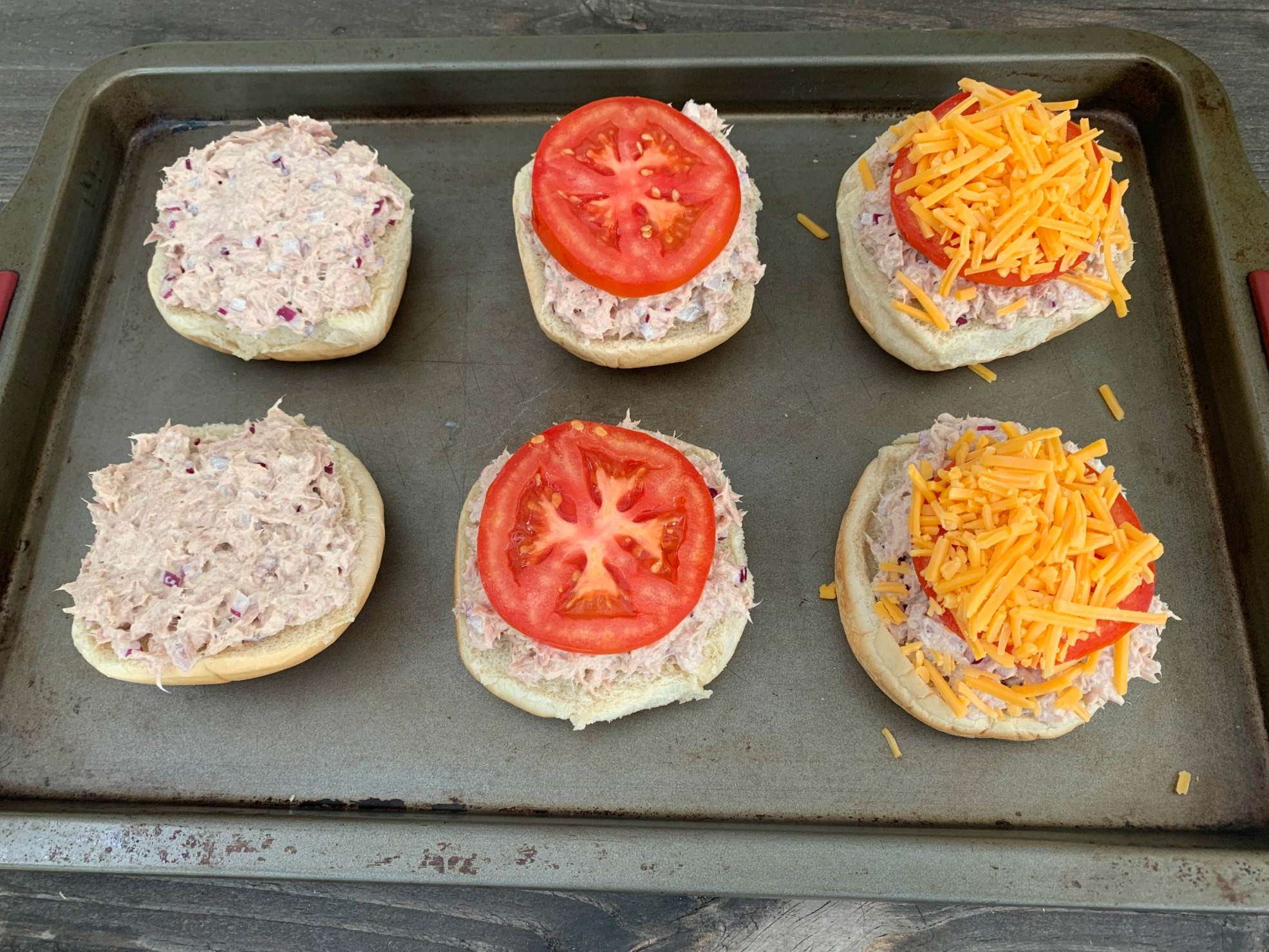 cookie sheet with 6 tuna melts in various stages of assembly