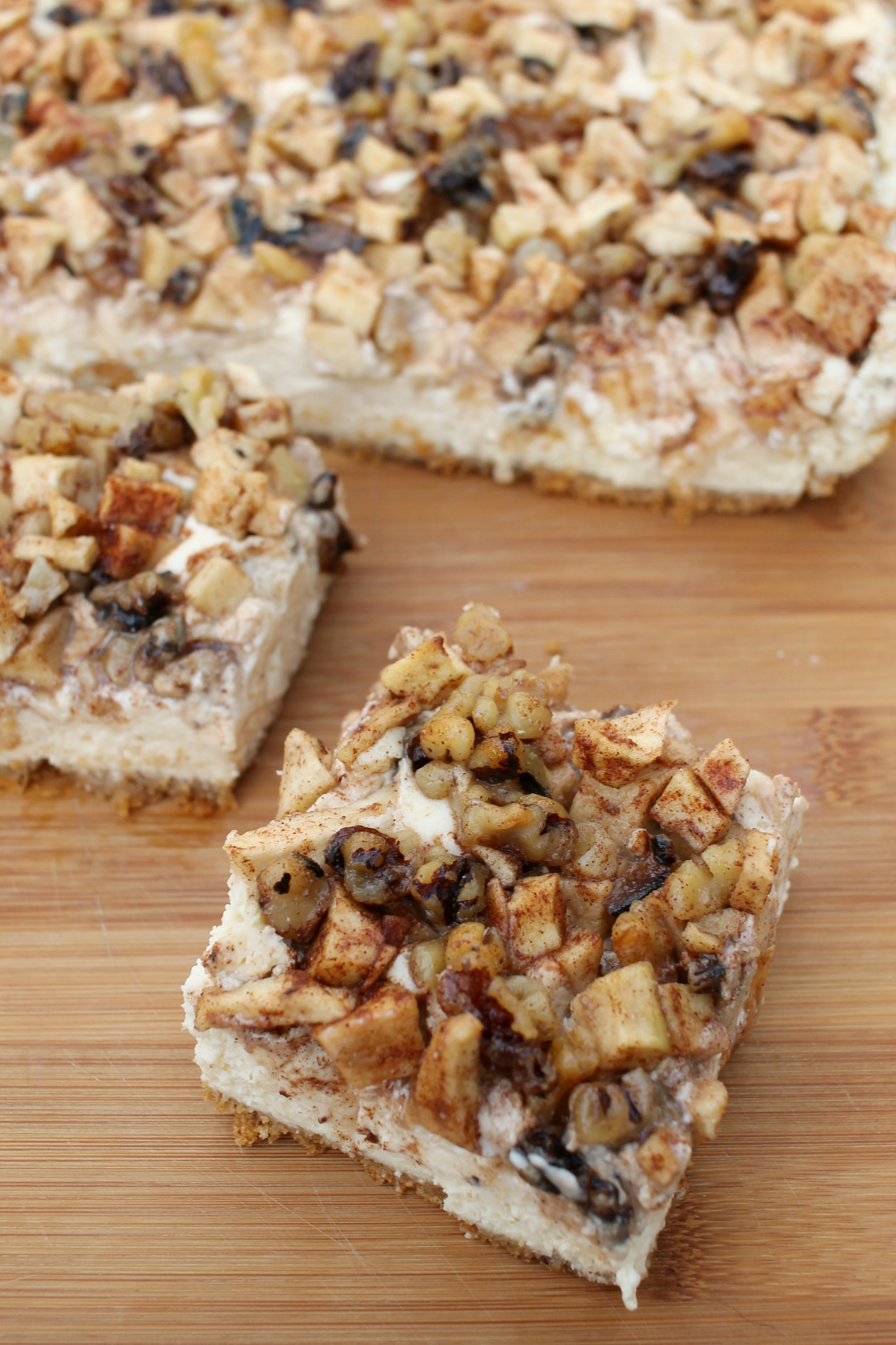 one slice of apple cheesecake bars pulled away from the rest