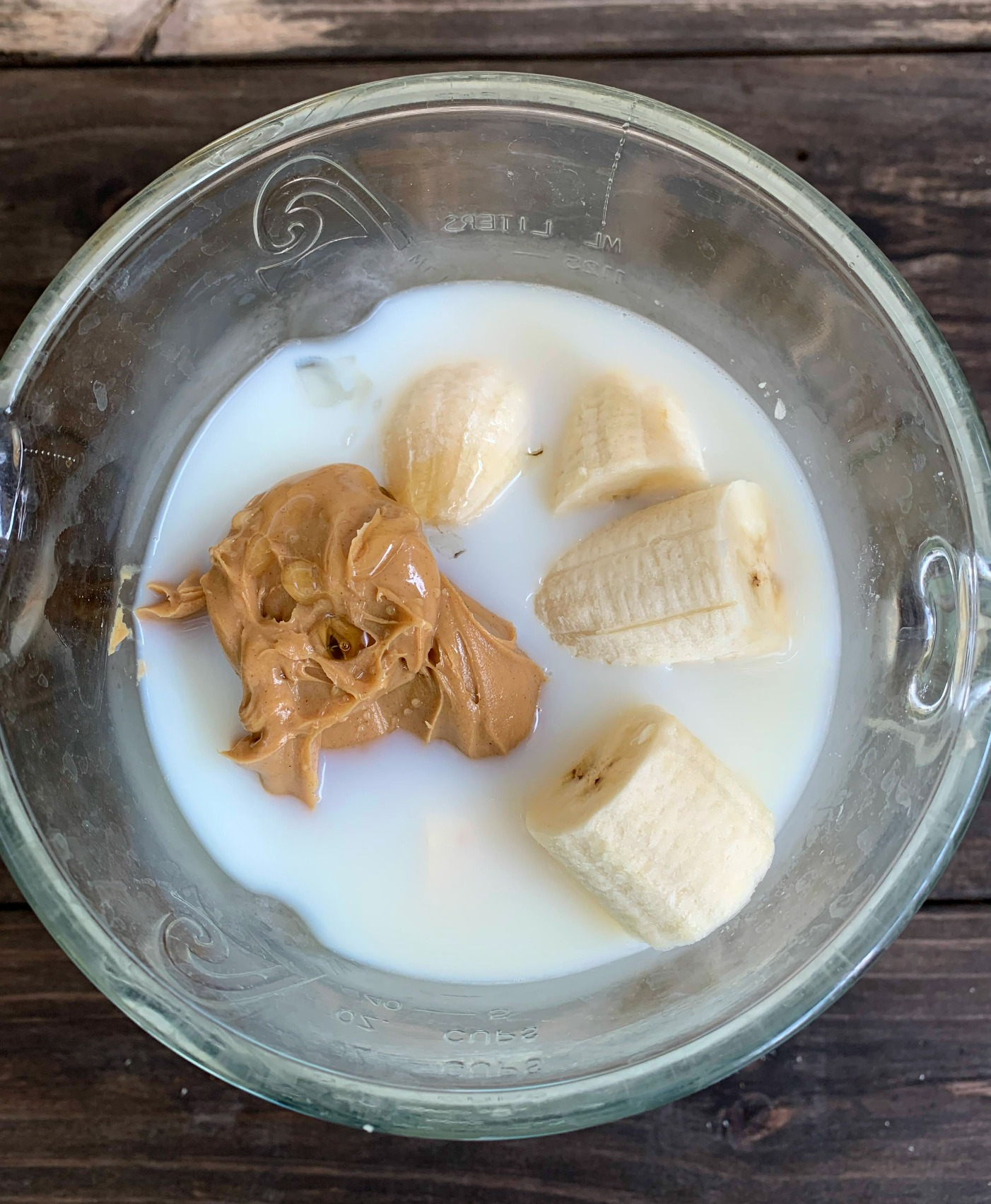 ingredients for peanut butter banana smoothie in blender before mixing