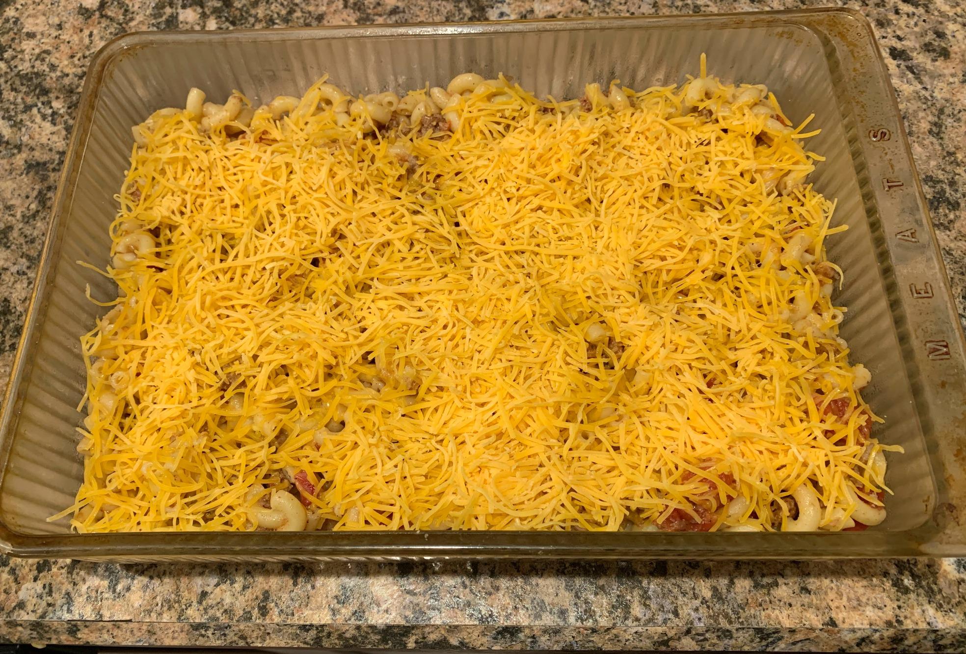 glass casserole pan with unbaked chili mac casserole