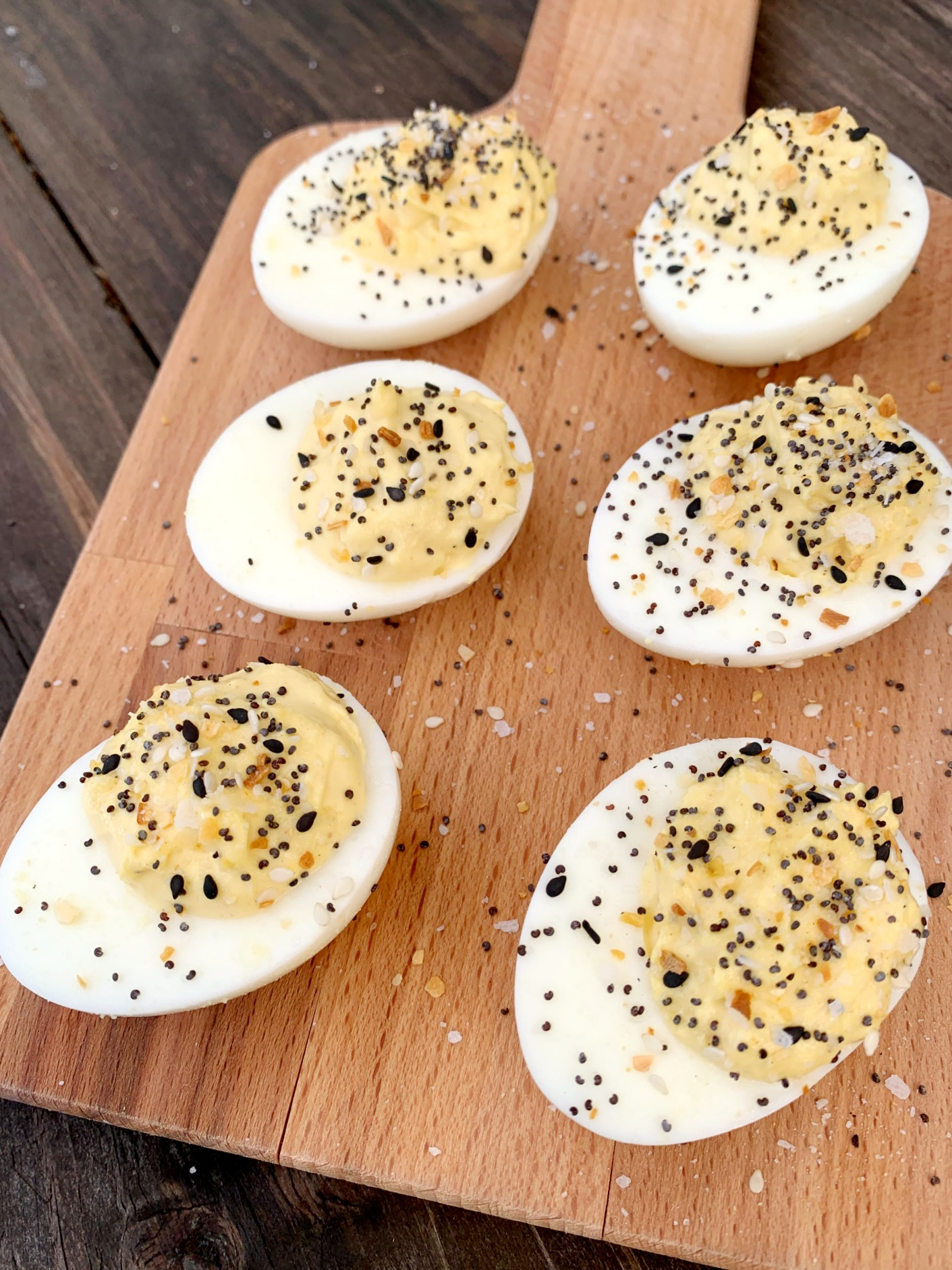 6 Everything But the Bagel Deviled Eggs on a wooden cutting board