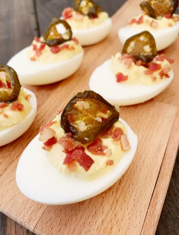 Jalapeno and Bacon Deviled Eggs on a wooden cutting board