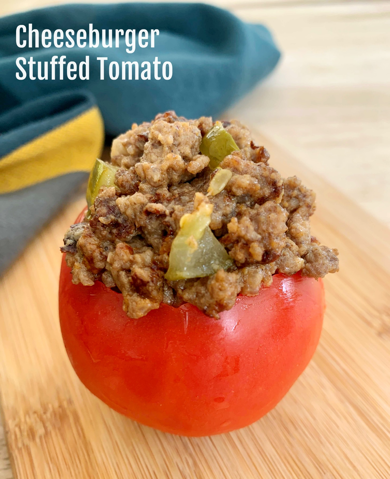 a tomato filled with cheeseburger mixture on a wooden cutting board