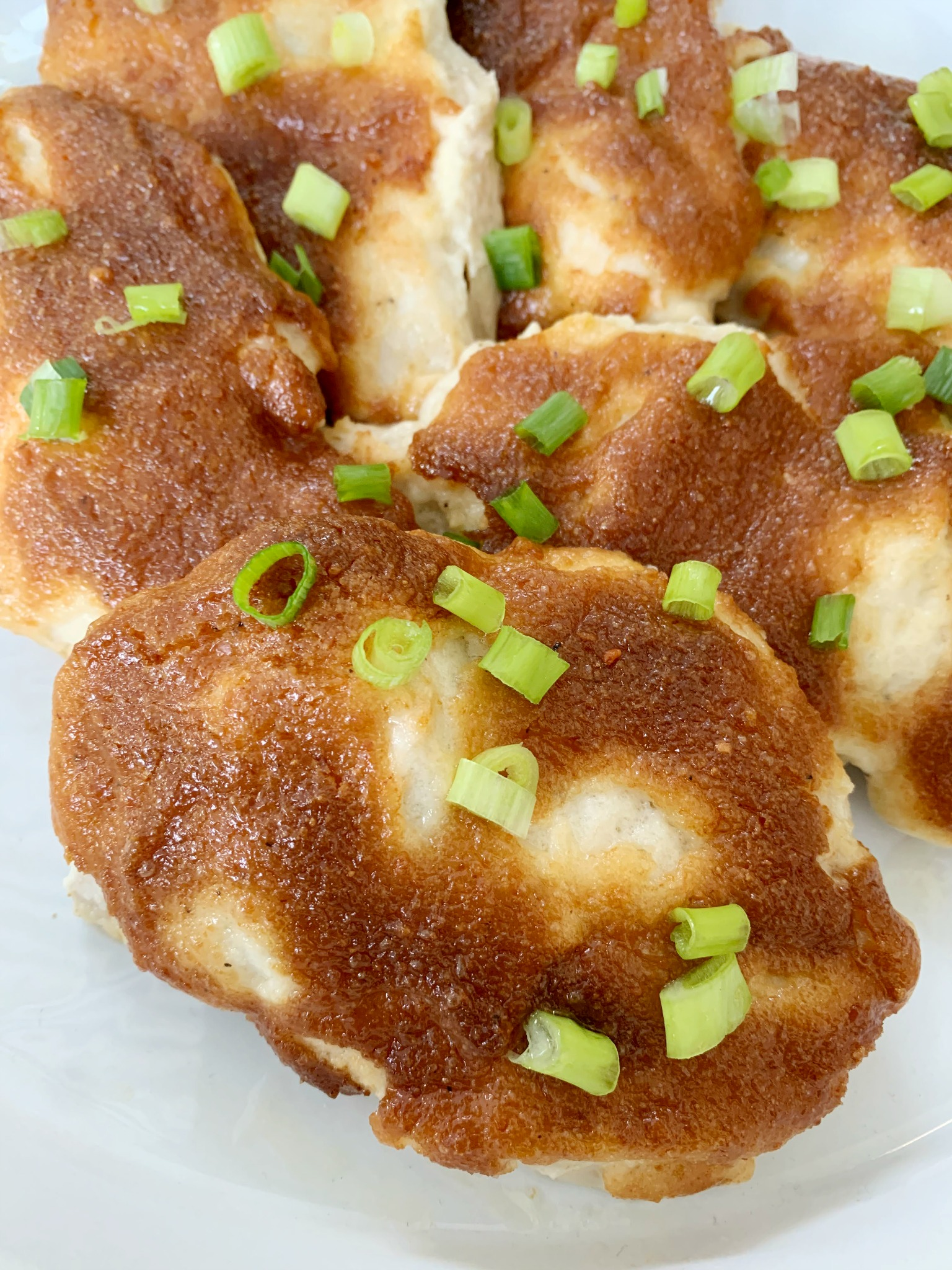 Melt In your Mouth Chicken on a white tray with chopped green onions