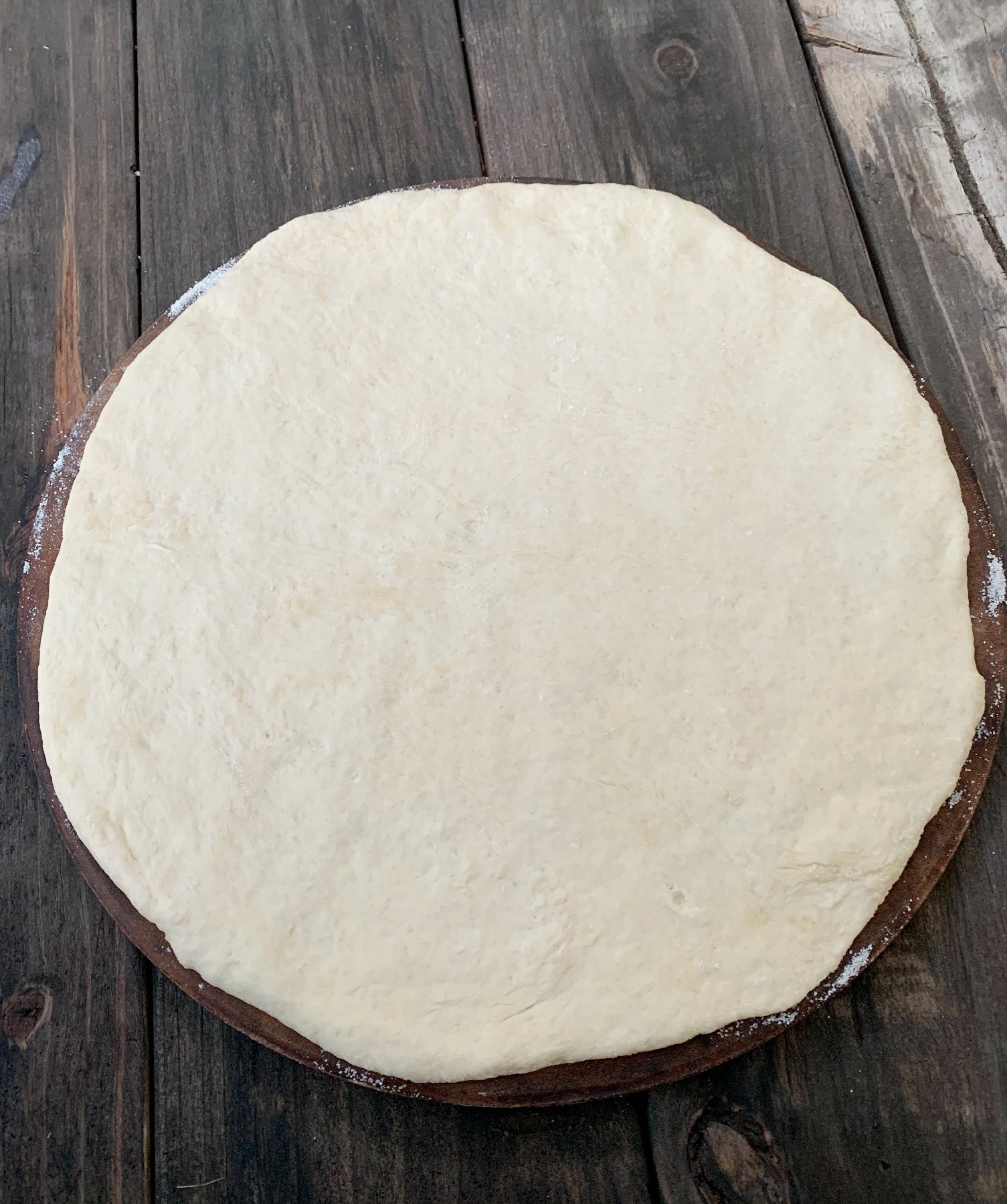 pizza dough rolled in a circle