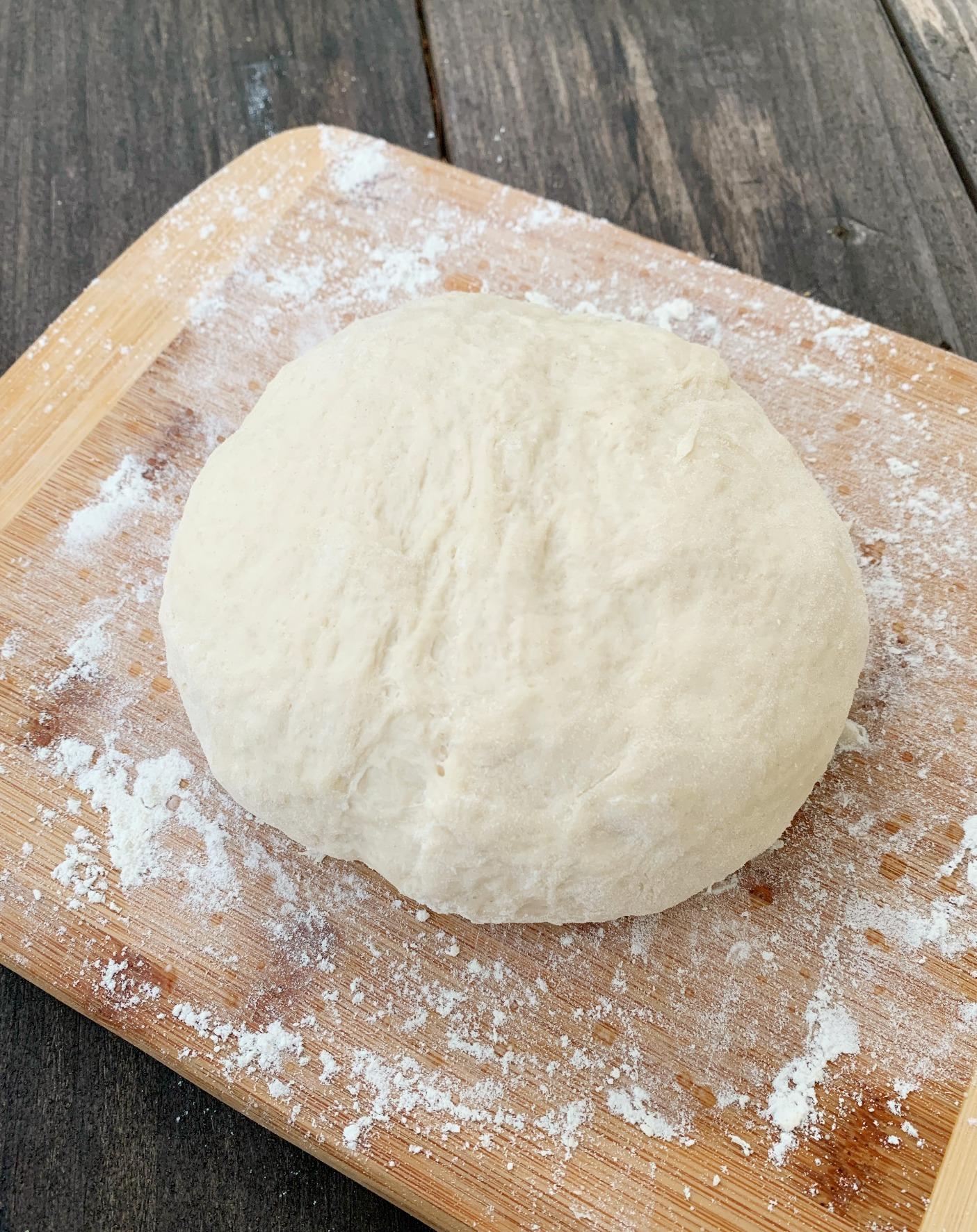 pizza dough in a ball on a floured cutting board