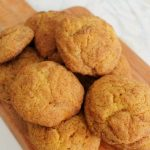 Pumpkin Snickerdoodles piled on a wooden cutting board