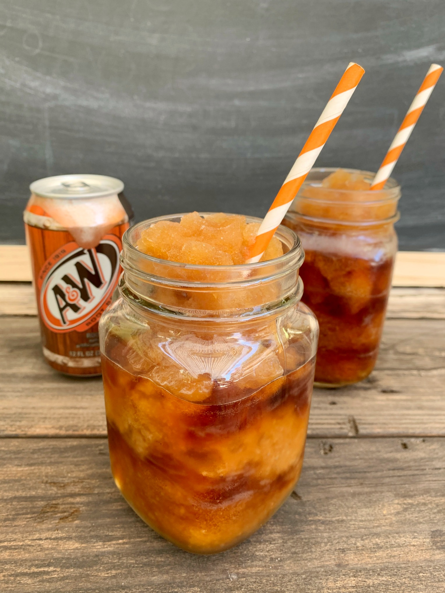 2 root beer slushies with paper straws and a can of root beer behind them