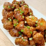 Sweet Chili Chicken on a white platter with chopped green onions