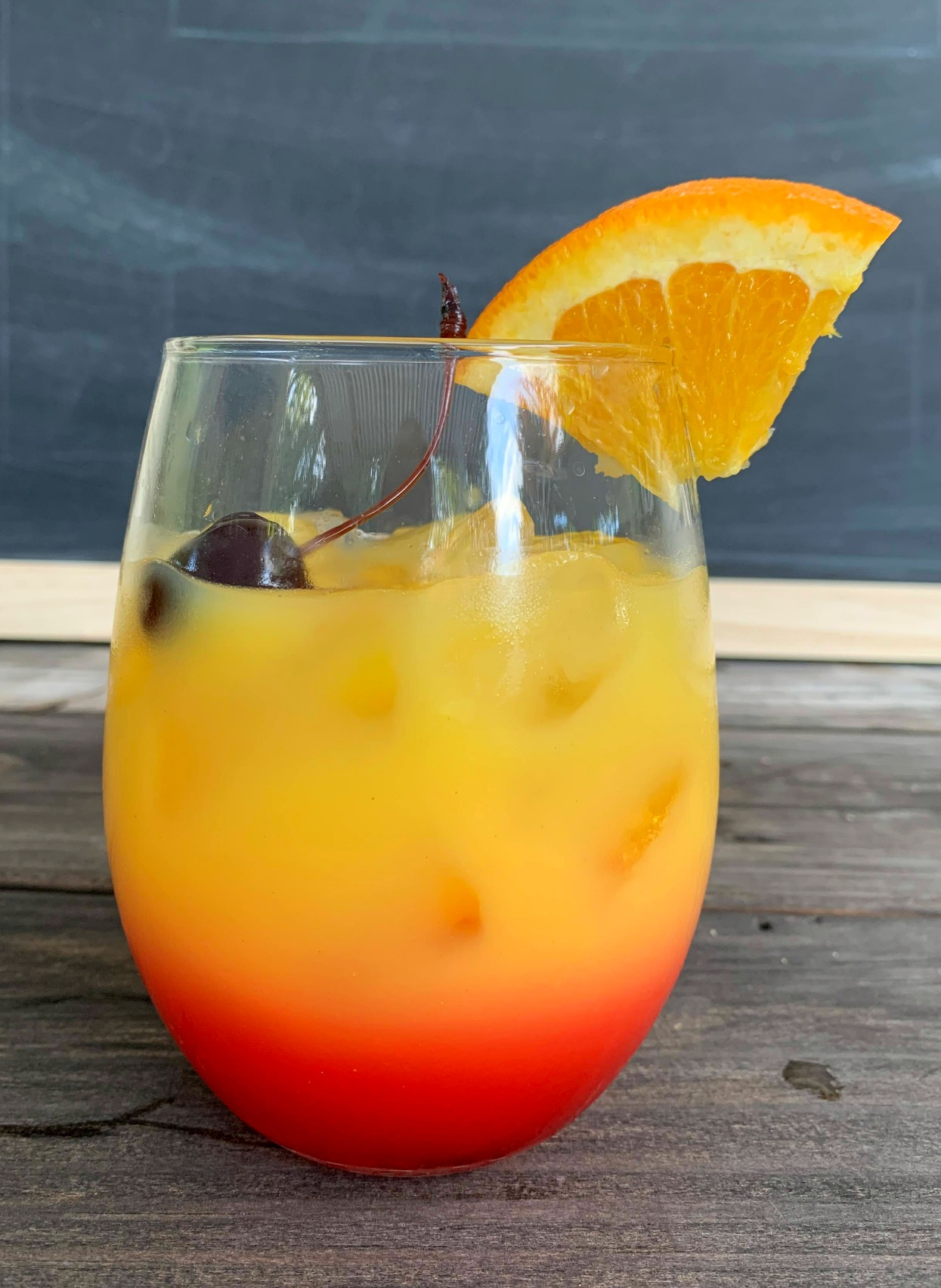 a glass of tequila sunrise with a cherry on top and an orange wedge garnish