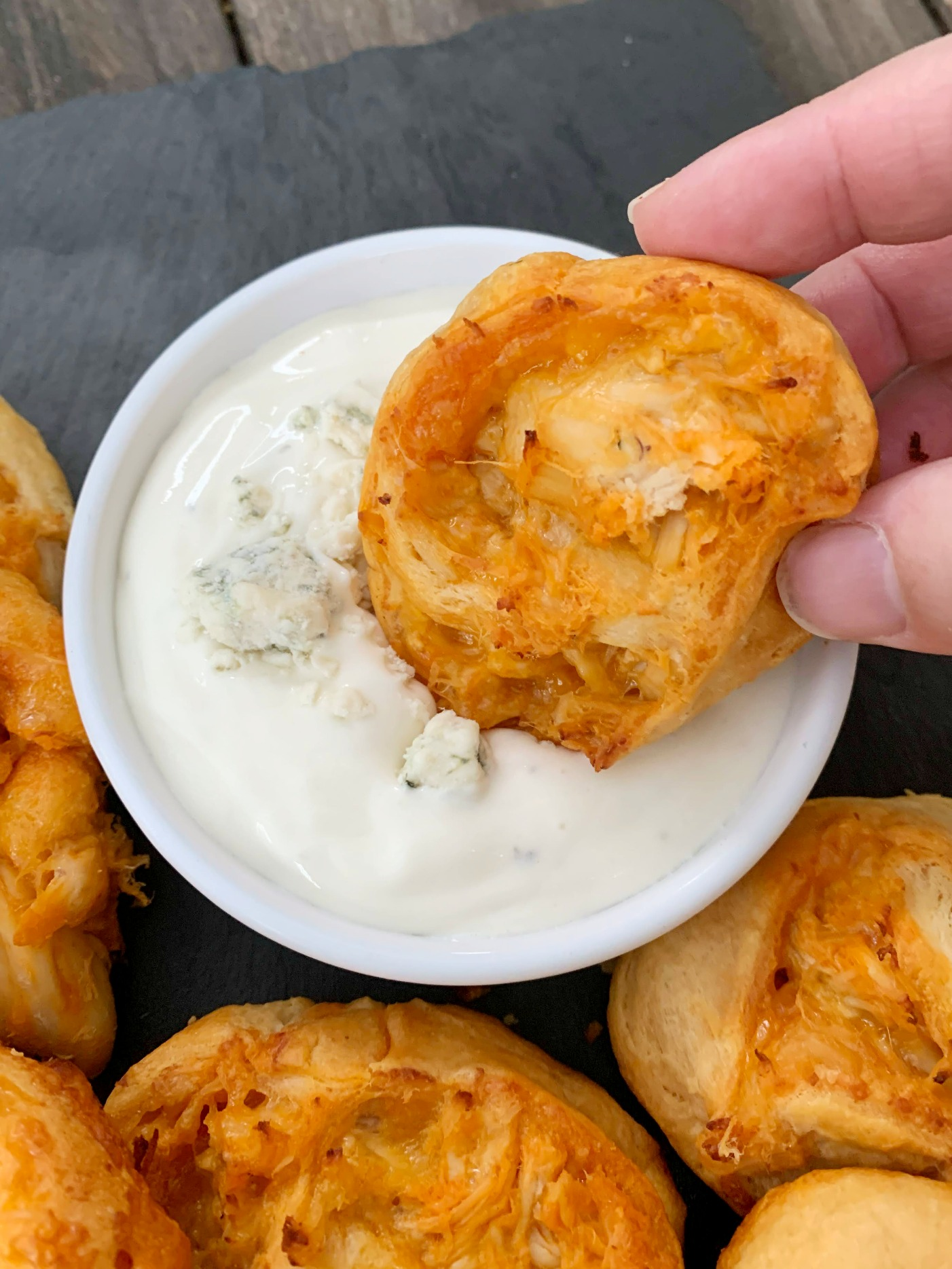 Buffalo Chicken Pinwheels being dipped into blue cheese dressing