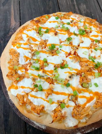 up close shot of buffalo chicken pizza drizzled with wing sauce and topped with chopped green onions