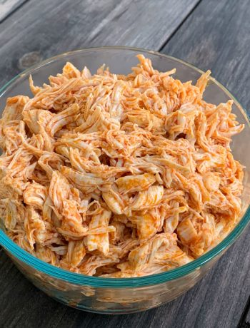 a glass bowl full of shredded buffalo chicken