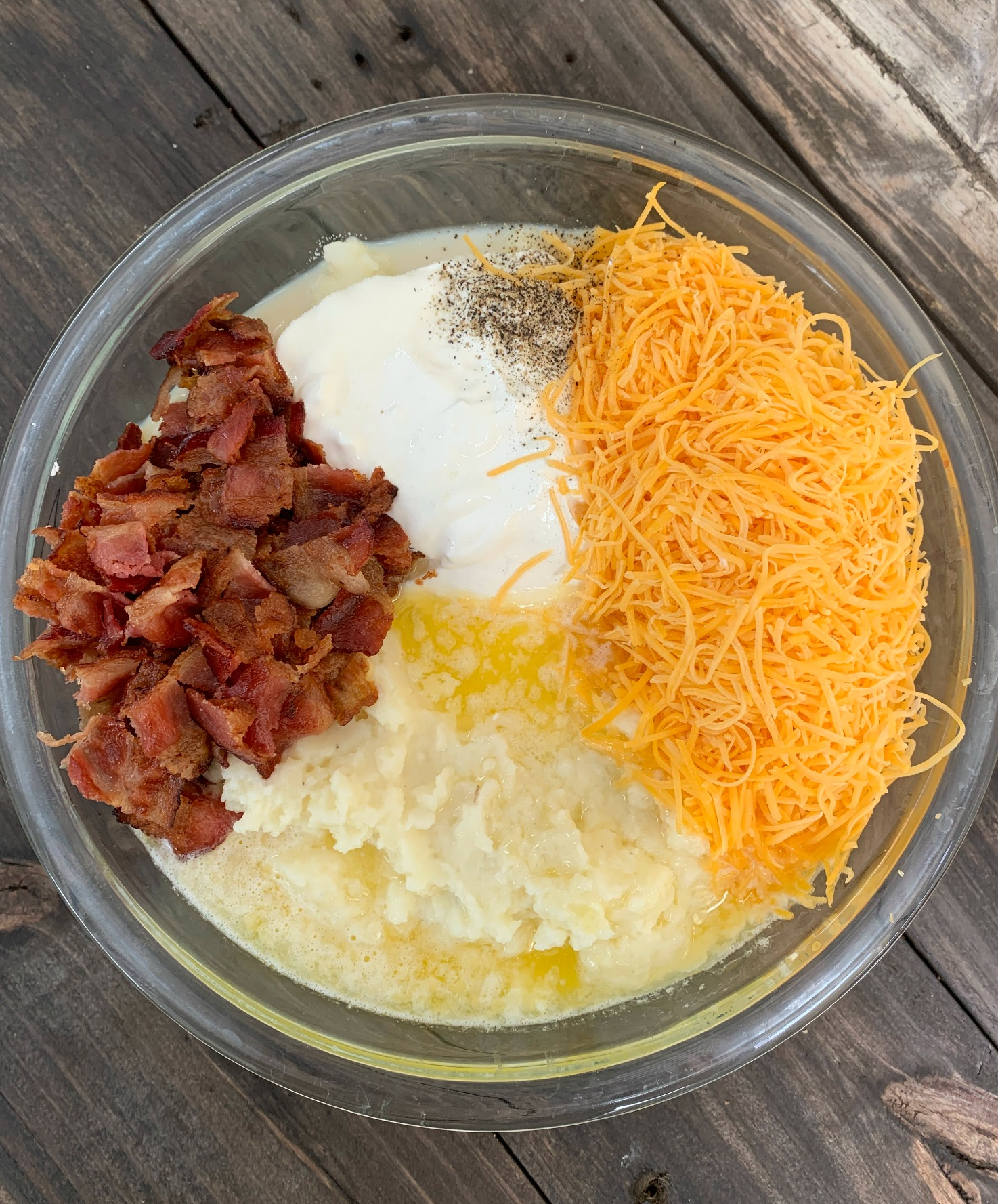 glass bowl with ingredients for white casserole dish with Loaded Mashed Potato Casserole