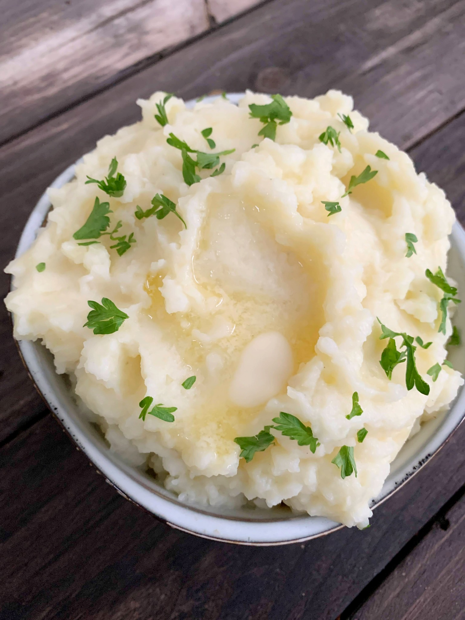 mashed potatoes in a bowl with melted butter and chopped parsley on top