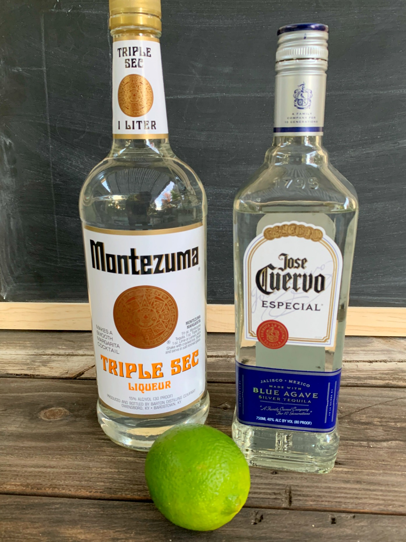bottle of tequila and triple sec with a lime in front