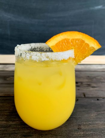 Orange Margarita with a sugar rim and wedge of orange