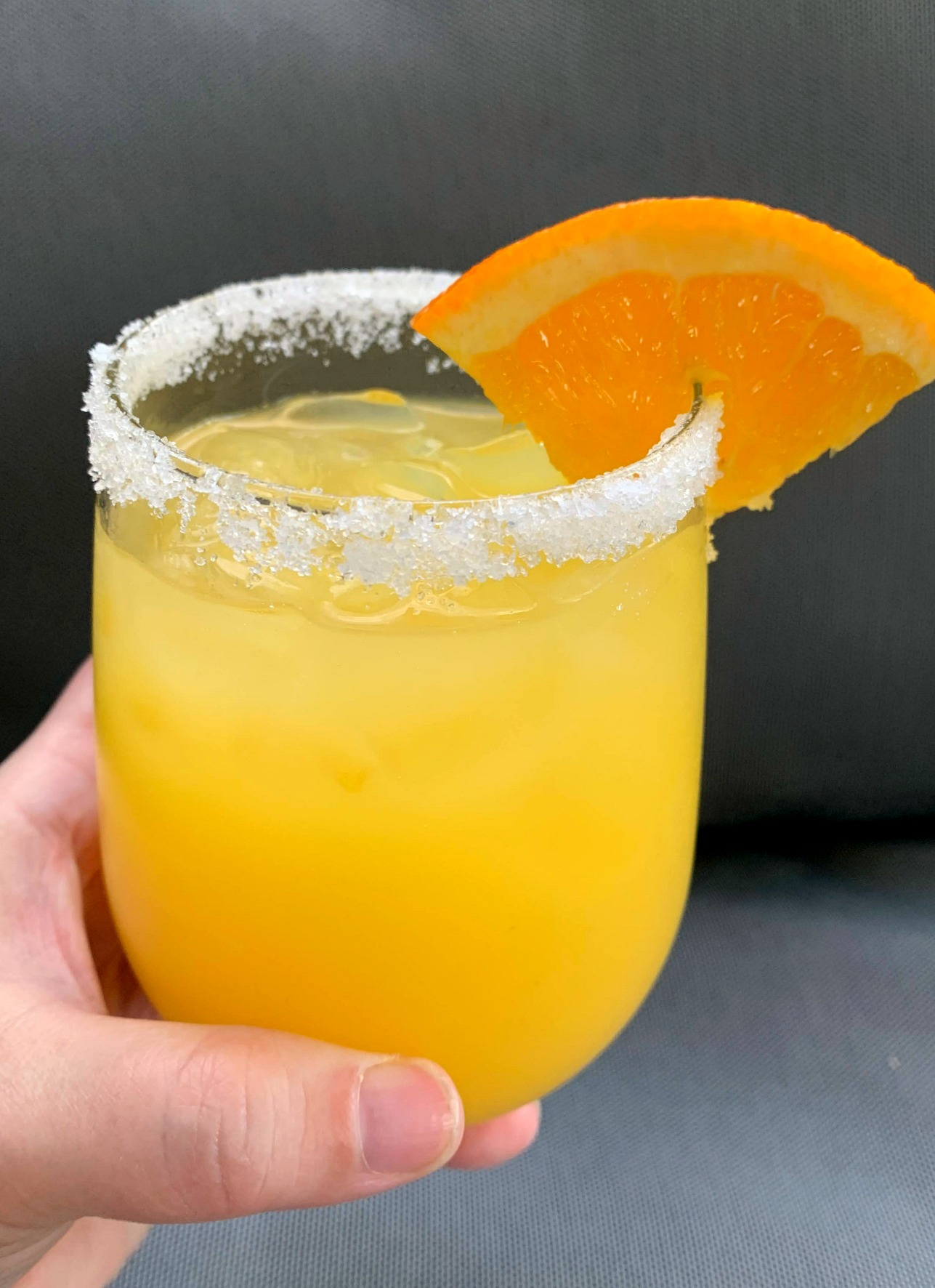 Orange Margarita with a sugar rim and wedge of orange