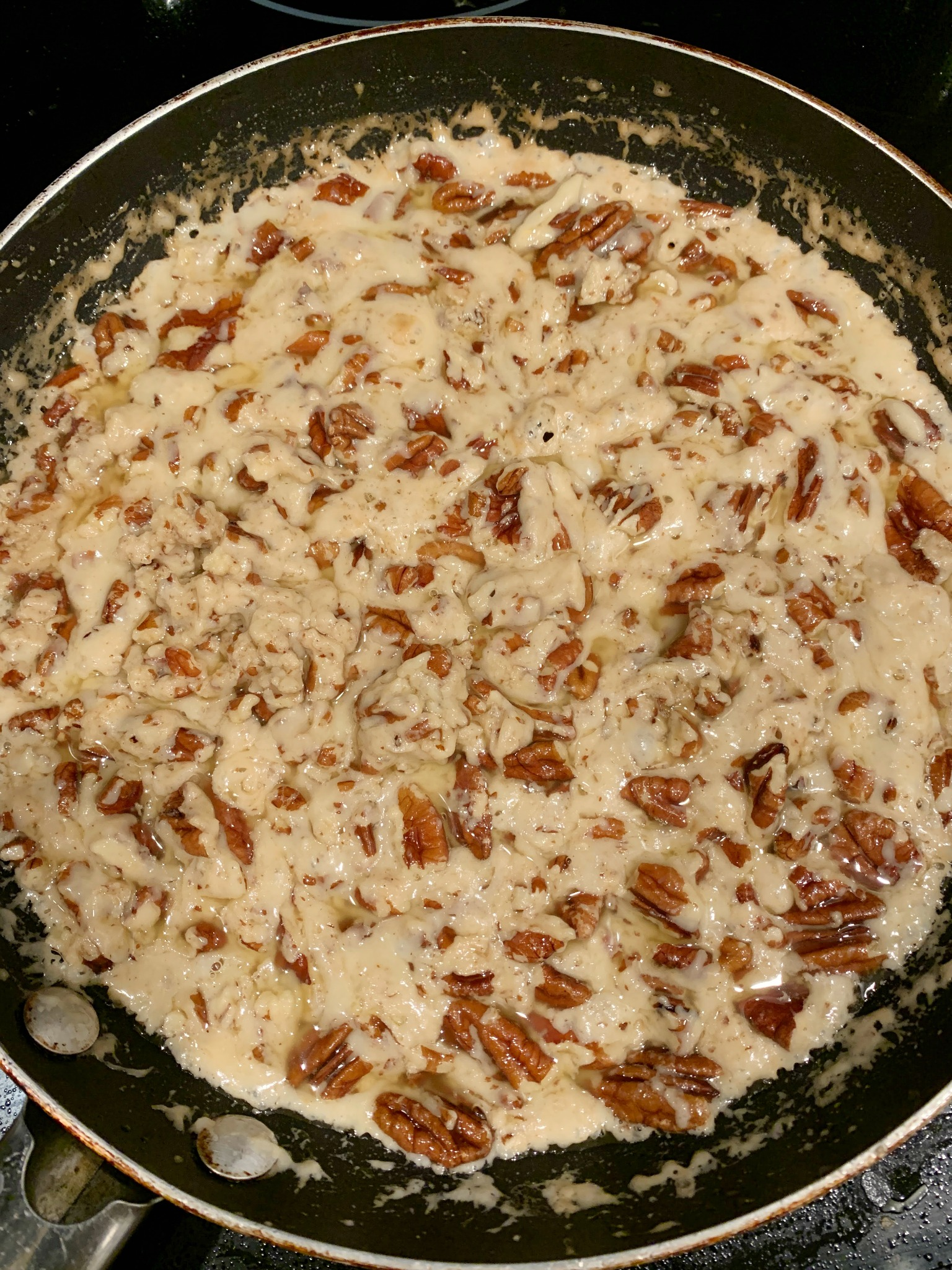 skillet with caramalized sugar and chopped pecans