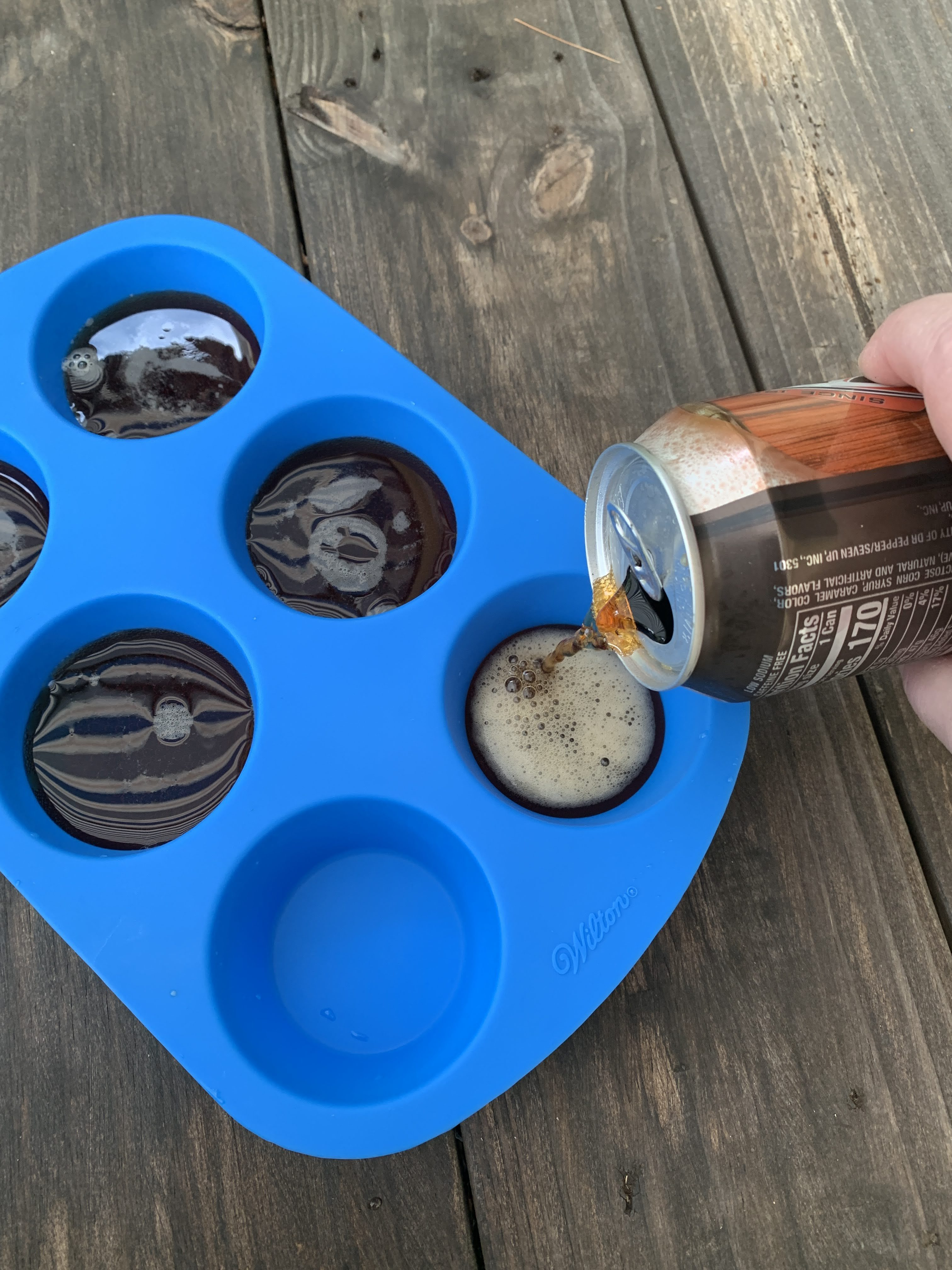 blue silicone cupcake mold with a hand pouring root beer into it