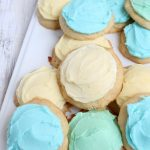 white tray of soft sugar cookies on pile with blue, yellow and green frosting