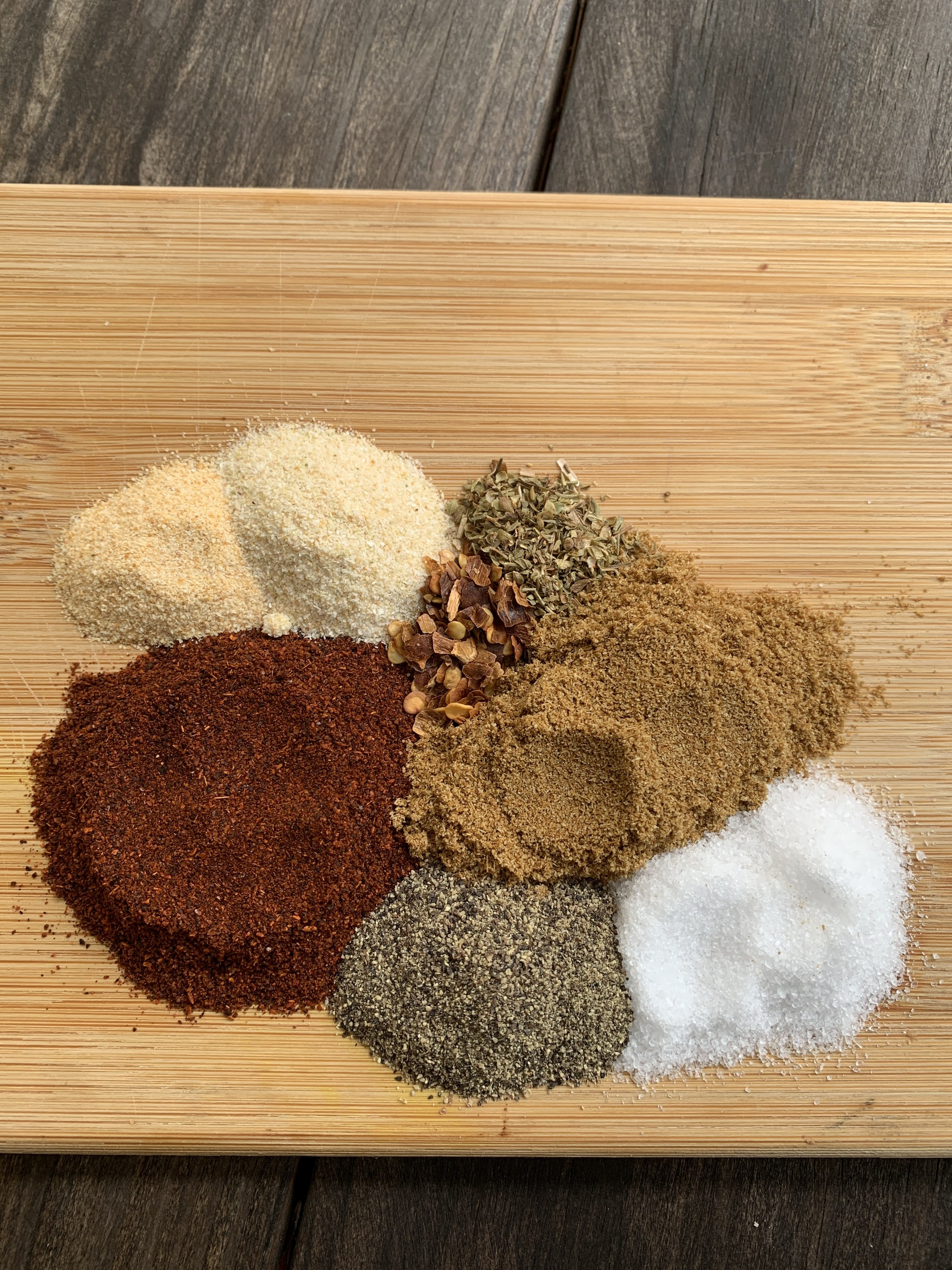 spices separated in piles on a wooden cutting board